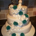 A teal and white rose wedding cake with personalized toppers