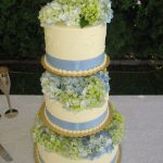Blue and green hydrangea blossoms on a pale yellow wedding cake