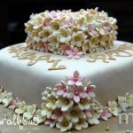 Brown and cream wedding cake with pink blush accents