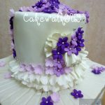 Chocolate mud cake with white frosting and purple flowers