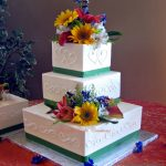 Elegant Square Ivory Buttercream Wedding Cake with Sunflowers and Lilies