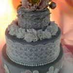 Grey wedding cake with white lace and flowers