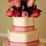 Hexagonal wedding cake with roses on top