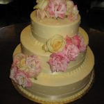 Light pink and yellow roses on a three-tier wedding cake