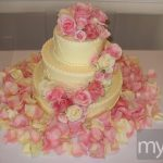 Light yellow wedding cake with pink roses and petal shower