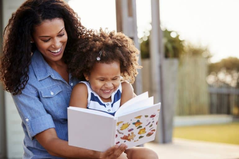 Young black girl reading book sitting on mumÕs knee outdoors