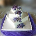 Square white tiered wedding cake with purple flowers
