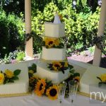 Sunflowers and yellow roses on light yellow wedding cakes