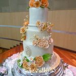Tall white cake with orange and sepia flowers