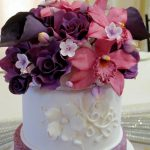 White, purple and pink cake with lots of flowers on top
