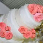 White wedding cake with pink roses and white dots