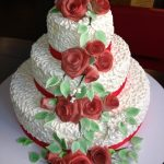 White wedding cake with red ribbons and roses